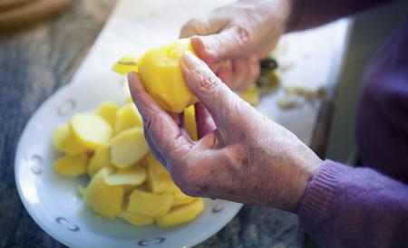 close-up van oudere vrouw handen snijden aardappelen in plakjes