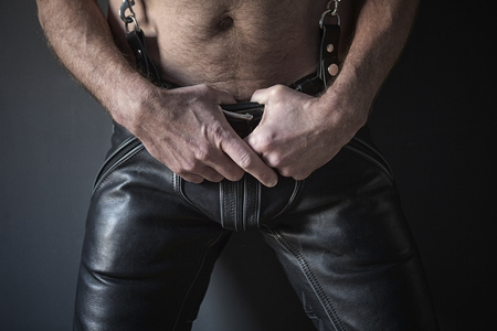black: closeup of shirtless man waering black leather pants