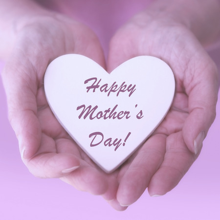 closeup of female hands holding white heart with the words Happy Mothers Day