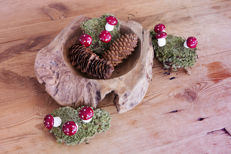potpourri: wooden bowl  with pinecones and moss and mushrooms on wooden table