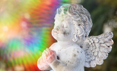 praying stone angel with a colorful sunbeam