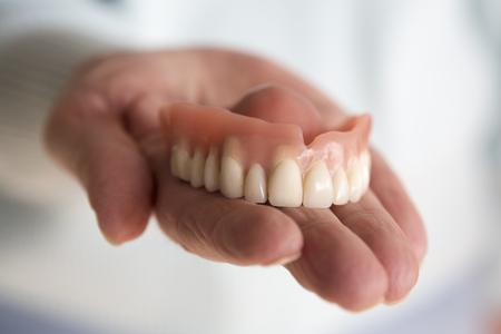 closeup of older womans hand holding a teeth denture Foto de archivo