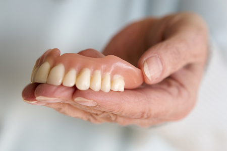 surrogate: closeup of older womans hand holding a teeth denture Stock Photo
