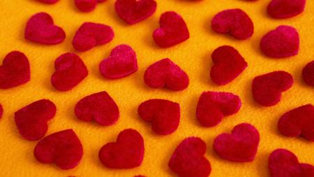 Close-up van veel rode zachte harten op gele tafel