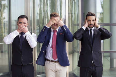 three handsome businessmen as the three wise monkeys Stock Photo