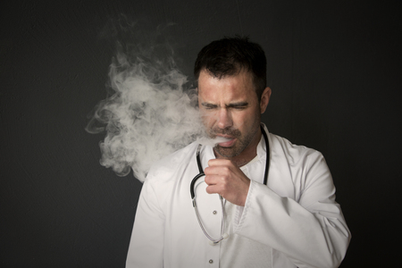 irresponsible: portrait of handsome doctor smoking and coughing Stock Photo
