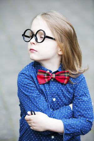 funny portrait of blond boy in shirt and bowtie with huge glasses looking arrogant Stock Photo