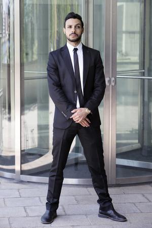 ガラスのドアの前でネクタイとスーツに立っているハンサムな男の肖像