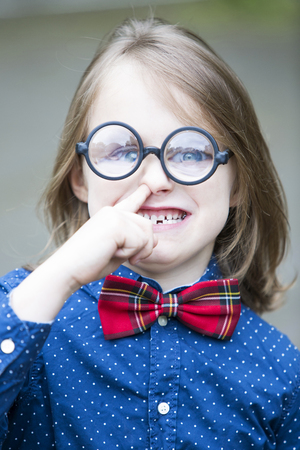 nose picking: funny portrait of boy with bow tie and big glasses picking his nose