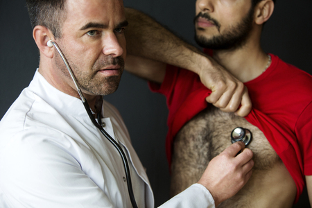handsome doctor with a stethoscope listening to patients heartbeat Stock Photo