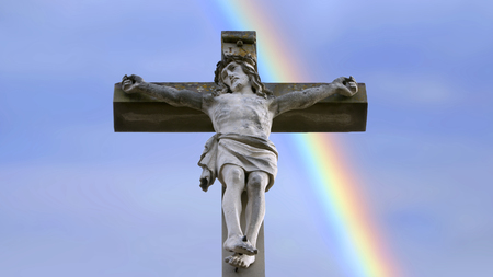 closeup of stone cross with Jesus and a blue sky with rainbow