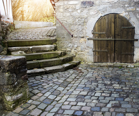 passageway: closeup of an old medieval cobblestone road and stone building