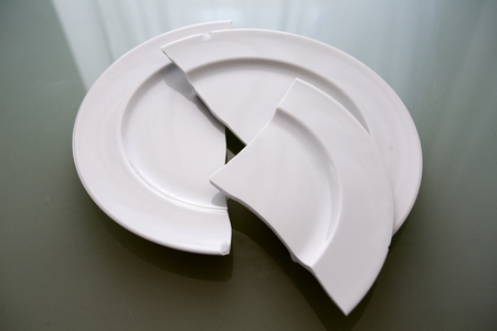 household accident: closeup of broken white plate on glass table Stock Photo