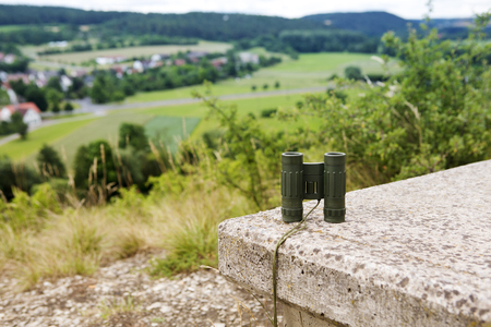 binoculars on a stone bench with view of a small town in the valley Stok Fotoğraf