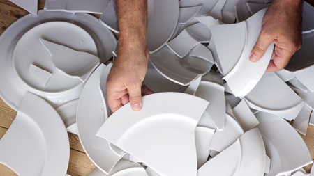household accident: hands picking up broken white plates from wooden floor