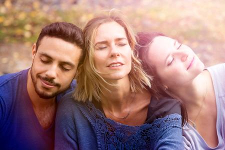 Retrato de tres amigos sentados afuera y relajarse bajo el sol