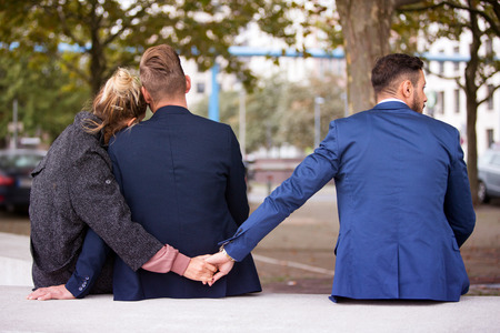 couple sitting on bench and hugging while the woman holding hands with another man
