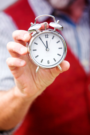 closeup of a man with a beard and a red vest holding a clock Stock Photo