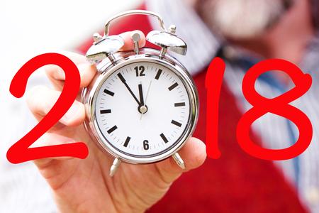 2018と時計を保持するひげを握る男 写真素材