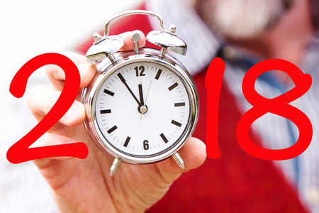 2018 and man holding a beard holding a clock Stock Photo