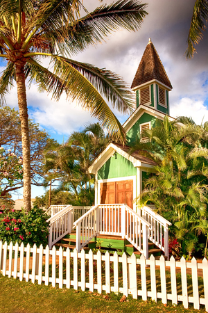 small wooden church on Hawaii surrounded by palm trees