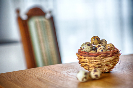 basket of quail eggs on wooden table and chair