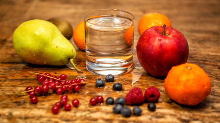 glass of water on rustic wooden table with fruits and berries