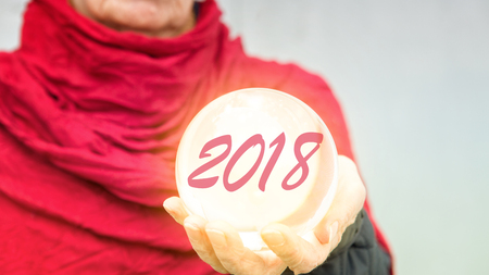 closeup of older woman holding glass sphere with 2018