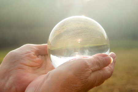 closeup of older womans hand holding a shiny glass sphere