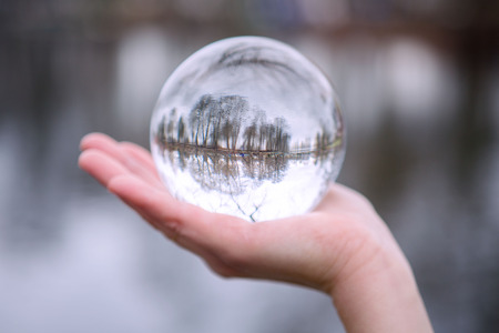 closeup of hand outdoors holding a glass sphere with reflection of trees