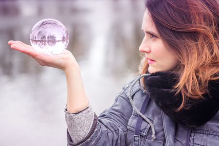 closeup of young woman outdoors holding a glass sphere