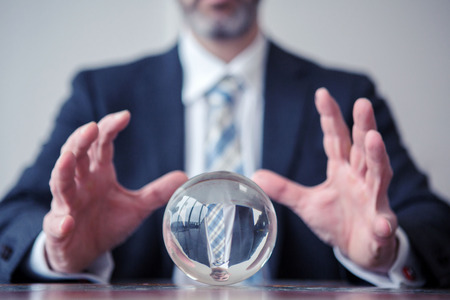 closeup of businessman looking at glass ball on table Stock Photo