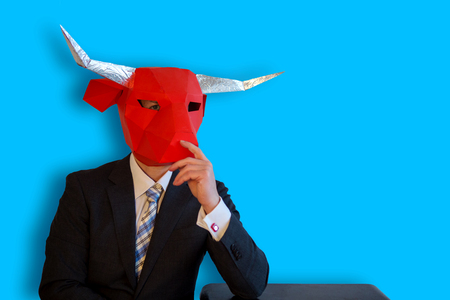 buisinessman with a bull mask sitting with a blue background
