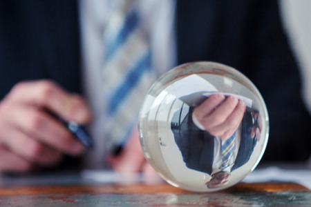 closeup of businessman signing papers in front of glass ball