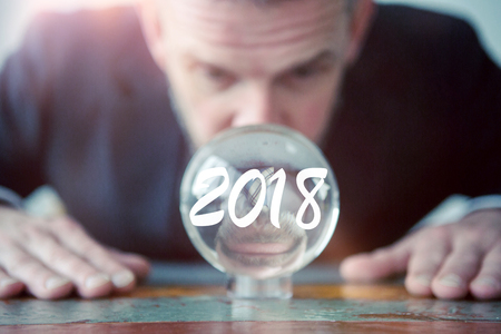 closeup of businessman looking at glass ball with the number 2018 스톡 콘텐츠
