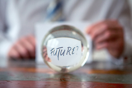 closeup of man holding paper with the word Future in front of glass ball Stock Photo