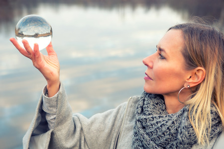 portrait of blond woman in front of lake holding up a glass ball Standard-Bild