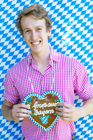 portrait of bavarian young man holding a heart-shaped gingerbread and blue white background Stockfoto