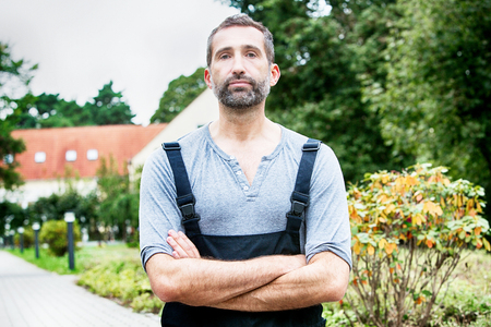 portrait of handsome man in dungarees standing outside Foto de archivo
