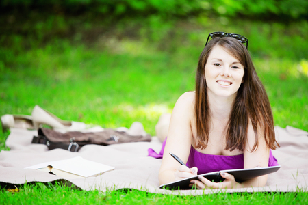 young brunette woman lying on blanket in park and studying Stock Photo