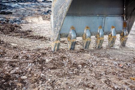 closeup of an excavator shovel digging in dirt at road construction