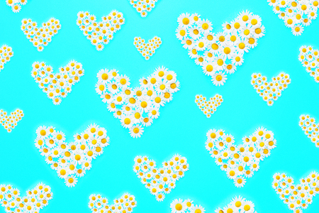 Daisies in different sizes of heart shapes on blue background