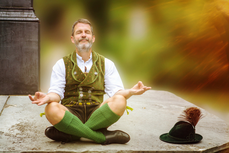 bavarian man sitting outddors on wall and meditating Stock Photo