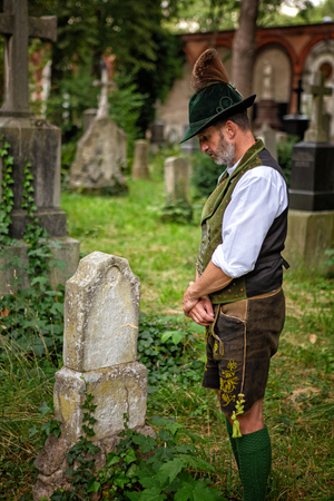bavarian man standing in front of a grave Stock Photo
