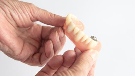 closeup of an older womans hand holding dentures