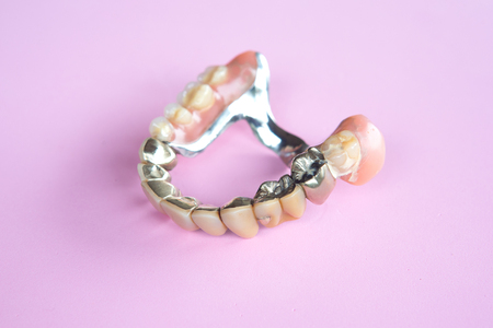 closeup of dental prosthesis on a pink background