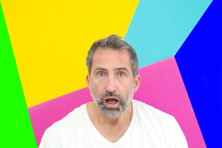 portrait of bearded man in front of colorful background looking surprised