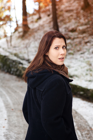 brunette young woman standing outdoors in the cold and looking scared