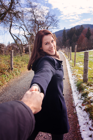 brunette young woman walking outdoors and holding hand of man