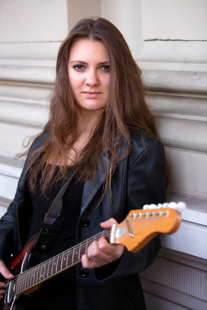 Young brunette woman in black leather jacket playing the guitar